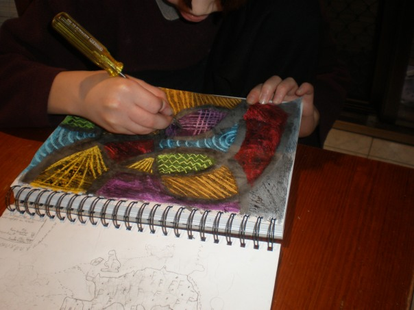 My son scratching out patterns on his piece.