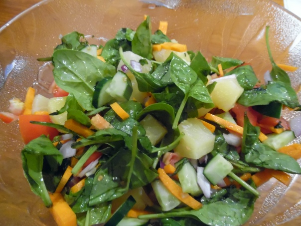 Salad: Spinach leaves, carrots, pineapple pieces, cucumber, tomatoes, and red onions